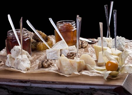 A set of cheeses on a wooden board with honey and jam
