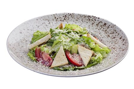 Caesar salad with chicken breast and anchovy sauce. On white background