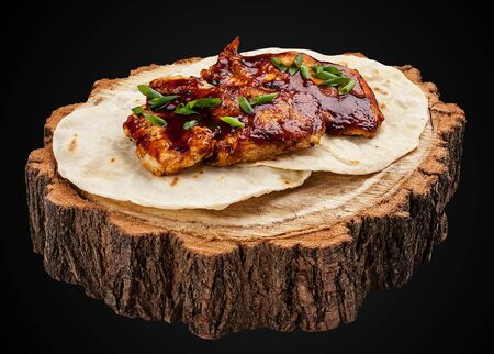 Grilled chicken fillet on a wooden slice