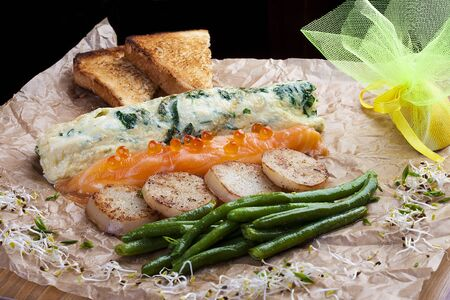 Combo salad: omelette with spinach, salmon with cheese, beans, potato croutons. 스톡 콘텐츠