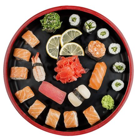 Sushi Set nigiri, rolls and sashimi served in traditional Japan black Sushioke round plate. On white background