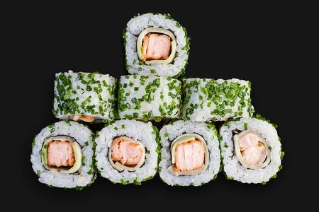 Sushi roll with roasted salmon and cucumber. Top view on dark background 스톡 콘텐츠