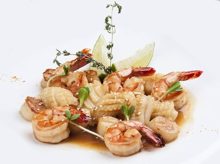 Scallops, squid and shrimp in teriyaki sauce. On a white background