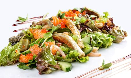 Salad with salmon belly and tobiko caviar on white background 스톡 콘텐츠