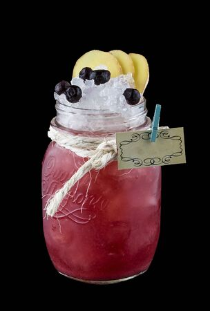 Currant lemonade with tarragon in a glass jar on a dark background