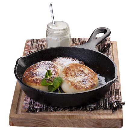 Pancakes with sour cream in a pan on the board. On white background 스톡 콘텐츠