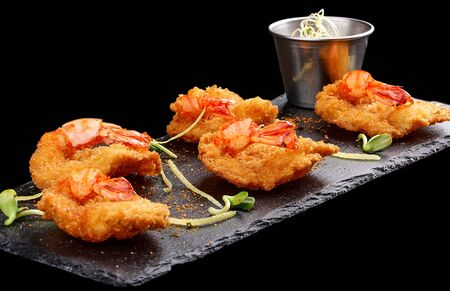 Tiger prawns in batter. Ebi tempura with spicy sauce on dark background