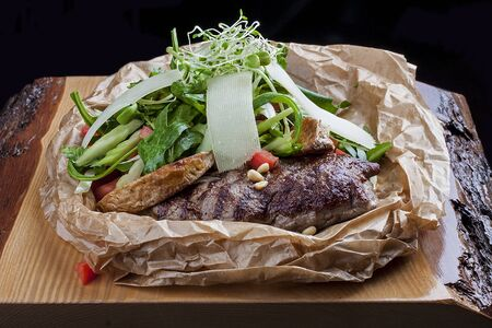 Veal steak with rocket and Parmesan cheese in parchment on wooden board