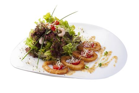 Mix salads with fried squid rings and shrimps with oyster sauce. On white background