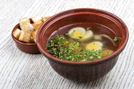 Chicken broth with quail eggs and crackers. Фото со стока