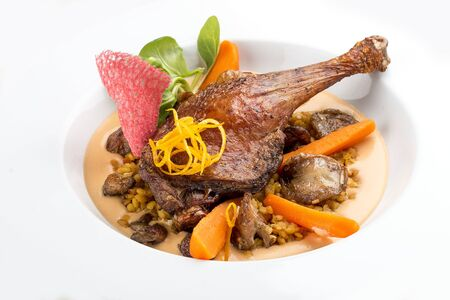 Duck leg with lentils and mushrooms on a white background 免版税图像