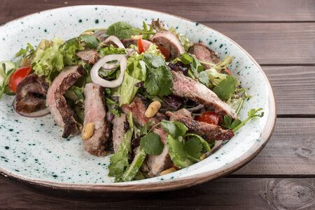Salad with roast beef and cherry tomatoes on a wooden background Banco de Imagens