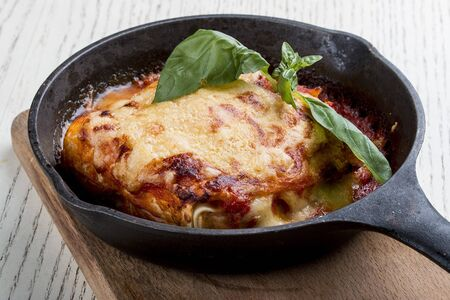 Lasagna in a cast iron pan on a wooden board. Traditional Italian dish