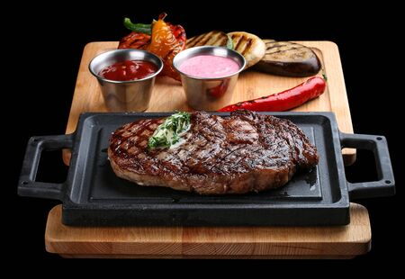Rib eye steak on wooden tray with grilled vegetables on dark background