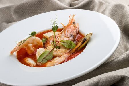 French bouillabaisse fish soup with shrimp, mussels and scallop. In a white plate on a textile background