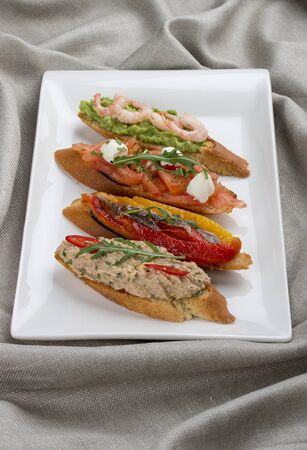 Brushetta snacks for wine. Variety of small sandwiches on a textile background Stock fotó