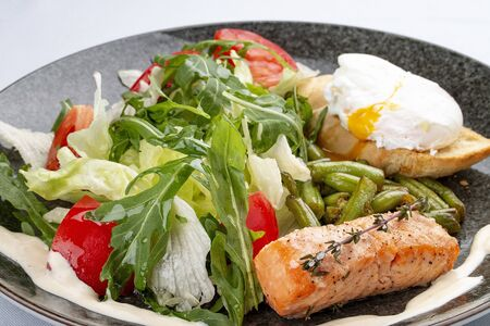 Salmon with poached egg, salad and asparagus beans