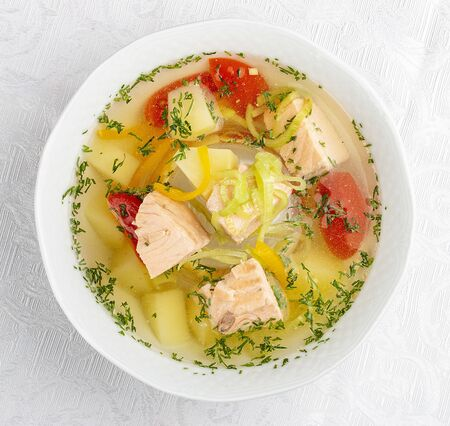 Soup with salmon and vegetables. On white background