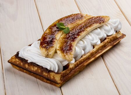 Belgian waffle with caramelized banana and cream. On a light wooden background