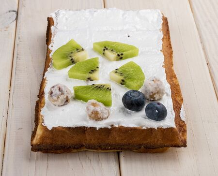 Belgian waffle with cream, kiwi and blueberries. On a light wooden background