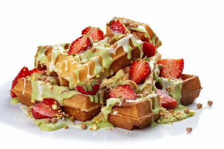 Belgian waffles with pistachio cream topping and strawberries. On white background