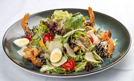 Fresh caesar salad on white bowl with parmesan cheese and shrimps. In a decorative plate 스톡 콘텐츠