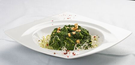 Spinach stewed in cream. In a white plate 스톡 콘텐츠