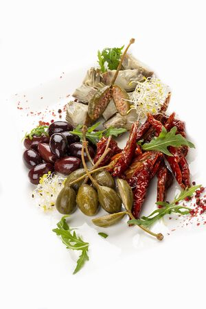 A plate of appetizers with Italian antipasti. Pickled anchovies, capers, mushrooms and sun-dried tomatoes. On light background 스톡 콘텐츠