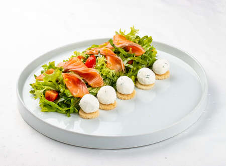 Salmon salad with cheese balls on a white plate