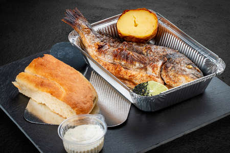 Grilled dorado with baked potatoes, matnakash and red sauce. Food delivery. Served on aluminum lunch box.