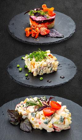 Set of salads on a dark background. Shuba salad, Olivier salad, crab meat salad.