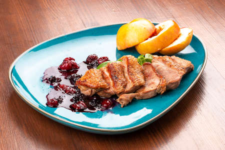 Magre duck breast with baked apple and berry sauce. On a decorative plate