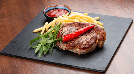 Pork steak with French fries and red sauce on a stone board