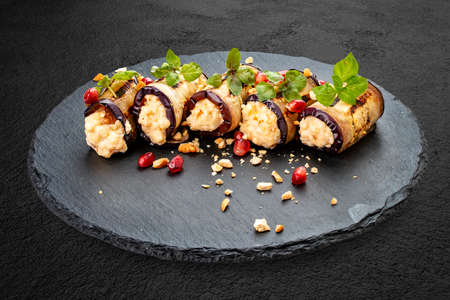 Eggplant rolls stuffed with cheese and nuts, on a stone board
