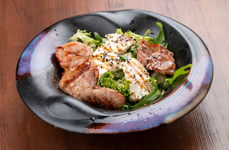 Duck breast salad with cream cheese and arugula. In a decorative plate