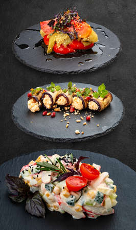 Set of salads on a dark background. Grilled vegetables, eggplant rolls, salad with crab meat