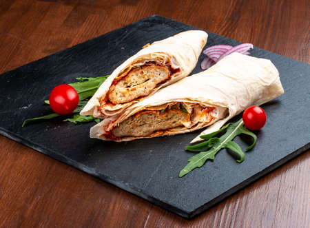 Lula kebab in lavash with salads and vegetables on a stone board