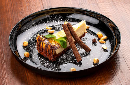 Cheesecake with nuts and chocolate tubes. On a decorative plate 免版税图像