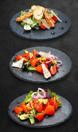 Set of salads on a dark background. Greek salad, Caesar salad, vegetable salad. 免版税图像