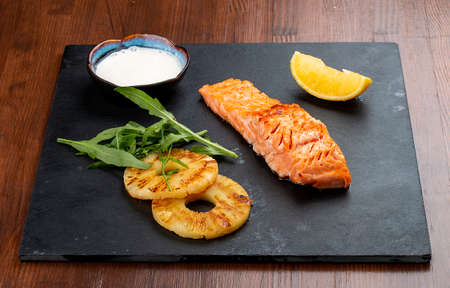 Salmon steak with grilled pineapple and white sauce on a stone board 免版税图像