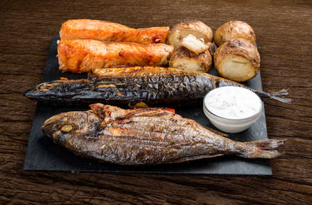 Stone board with different tasty cooked meat on wood background. Assorted meat and fish