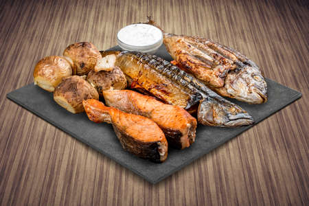 A selection of various barbecued gourmet meats on a black board with a rustic timber background. Assorted meat and fish