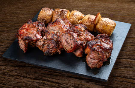 Stone board with different tasty cooked meat on wood background. Pork kebab, potatoes