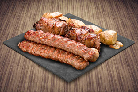 A selection of various barbecued gourmet meats on a black board with a rustic timber background. Pork kebab, lyulya, potatoes.