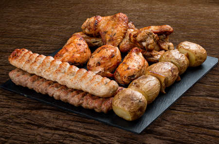 Stone board with different tasty cooked meat on wood background. Assorted meat