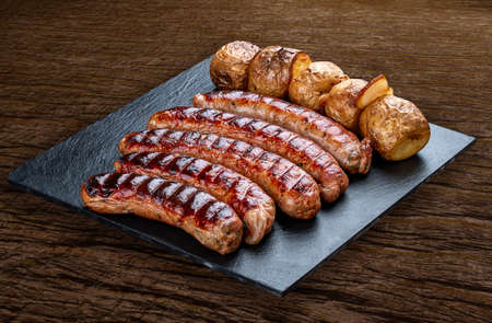 Handmade sausages with baked potatoes on a black board with a rustic timber background.