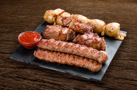 Stone board with different tasty cooked meat on wood background. Pork kebab, lyulya, potatoes.