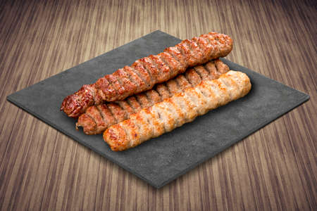 A selection of various barbecued gourmet meats on a black board with a rustic timber background. Various meat kebab