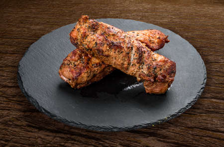 Stone board with different tasty cooked meat on wood background. Chiken fillet grilled