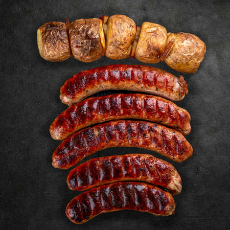 Handmade sausages with baked potatoes on a black board with a dark stone background. Top view